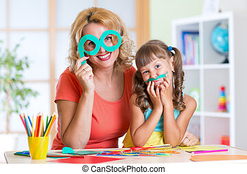 Child with woman have a fun cutting out scissors paper in...