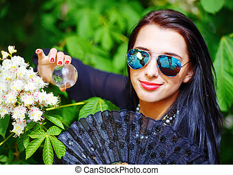 Beautiful Girl with flowers, and sunglasses, posing next to...