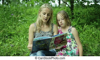 Mother reading book to her daughter in the park - Mother...