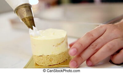 whipped cream decorate cake topping - hands squeezing...