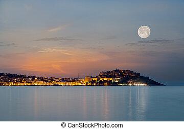 Full moon over Calvi citadel in Balagne region of Corsica -...