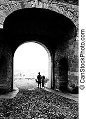 Bergamo Alta - A young couple exiting from the antique arch...