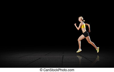 At full speed - Young woman athlete running fast on dark...