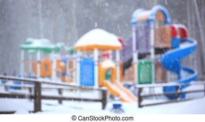 Park playground covered in snow. Children with mother playing on the playground in the winter during snowfall