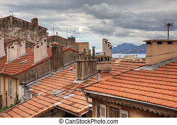 Old houses with tiled roof and dramatic cloudy sky Cannes,...