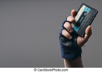 male hand with glove holding an old music tape