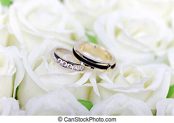 Two wedding rings on white roses bouquet.