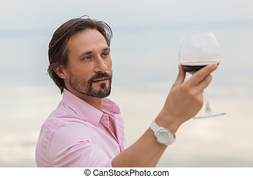 Sommelier analyzing a glass of red wine isolated on blue sky...
