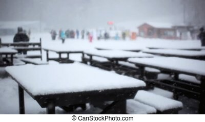 Chairs and table made from snow at Ski bar during snowfall in blizzard. Blurred background