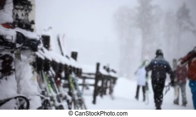 snowboards and skis standing on a wooden rack in a blizzard gray winter day at resort during snowfall