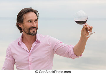 Sommelier tasting red wine in glass Smiling man is satisfied...