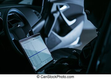Hacker in a Car - Hacker with Laptop in a Car at Night...