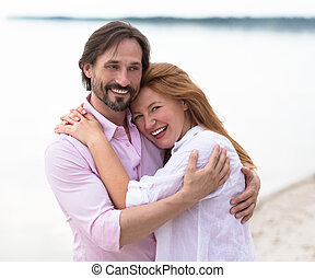 Middle-aged couple - Couple walking on beach arm in arm and...
