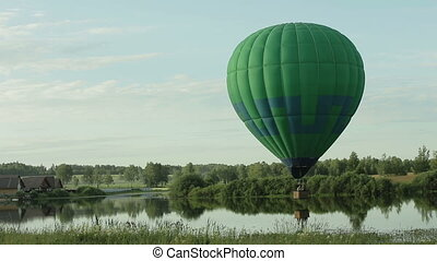 Hot air balloon flying over lake - Hot air balloon touches...