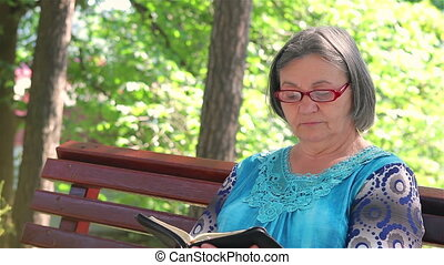 Elderly woman reading bible - Senior woman reading bible on...