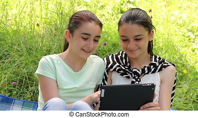 Girls playing on digital tablet outdoors on grass.