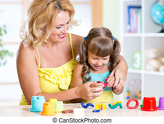 child and mother making by hands and playing with clay