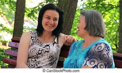 Mother with her daughter in park - Mother talking with her...