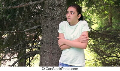 Sad girl lost in forest looking around.