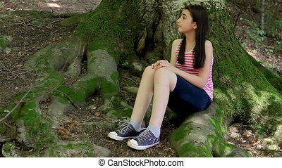 Scared girl lost in forest looking around and crying.