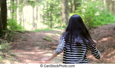 Scared teenage girl running in the forest. Someone is...