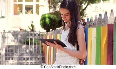Schoolgirl using tablet pc in front of the school