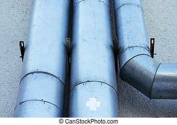 The pipes on the exterior wall of a building close-up