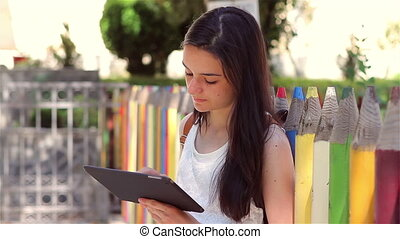 Student girl shows tablet pc - Beautiful teenage girl...