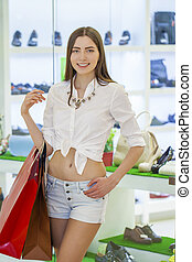 Shopping, young beautiful woman on the background showcases...