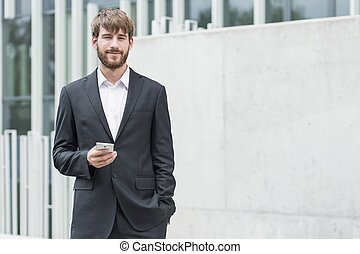 Smiling young businessman - Young man in business suit is...