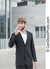 Sip of coffee - Businessman is standing outside company...