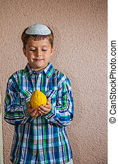 The boy in white skullcap is holding etrog - Etrog - ritual...