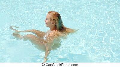 Woman Splashing Water While Enjoying at the Pool - Side View...