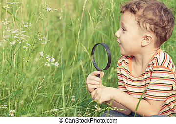 Happy little boy exploring nature with magnifying glass at...