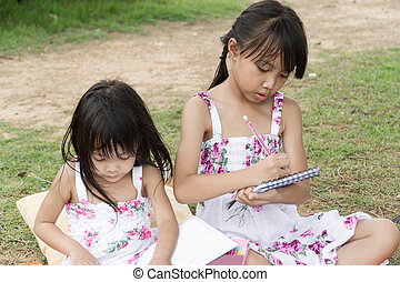 Little asian girl use pencil writing on notebook for writing book in the park and her sister writing too