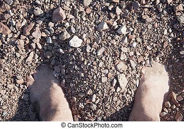 Male legs on pebble.