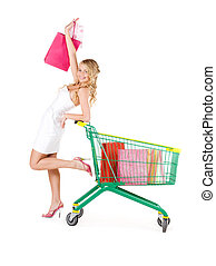 shopper - happy woman with shopping bags and cart over white
