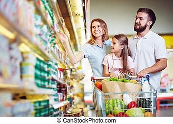 Buying food in hypermarket - Happy family choosing dairy...