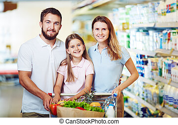 Visiting hypermarket - Cheerful family with shopping cart...