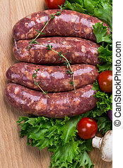 uncooked raw sausages on wooden board - uncooked raw...