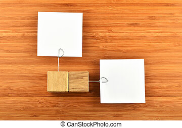 Two paper notes with wooden holders different directions on wood