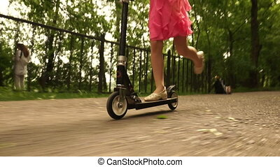 Girl playing mini scooter, kick scooter in park close-up