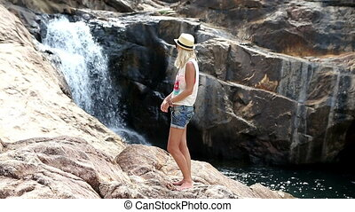 Admiring Waterfall - Young woman showing her boyfriend a...