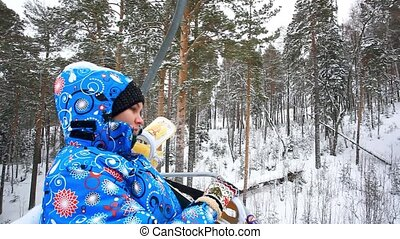 Pregnant smiling woman rides a lift up the mountain in a ski suit
