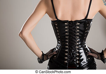 Rear view of sexy fetish woman in black corset - Rear view...
