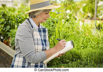 Working in a greenhouse - Mature woman in a greenhouse...