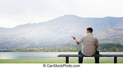 Fat man sitting on bench with his back and pointing away...