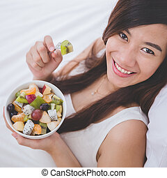 Beautiful pregnant woman with a bowl of fruit, white background