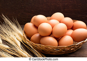 chicken egg in a basket over a rustic background