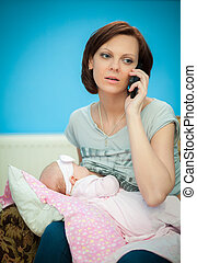 Multi-tasking mother - adult woman breastfeeding her newborn...